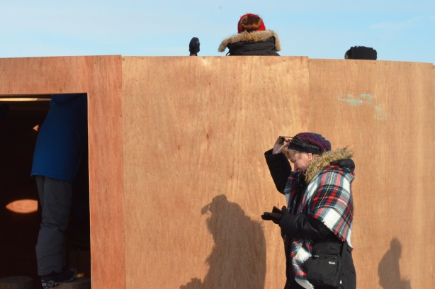 a woman in a tartan scarf walks past 'Mind Station', an art installation at Woodbine Beach made of plywood