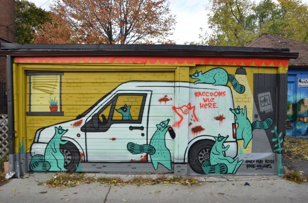 mural on a garage in an alley, Feel Good Lane, by Emily May Rose and of a white van with lots of green raccoons around it, on top of it, and in the drivers seat