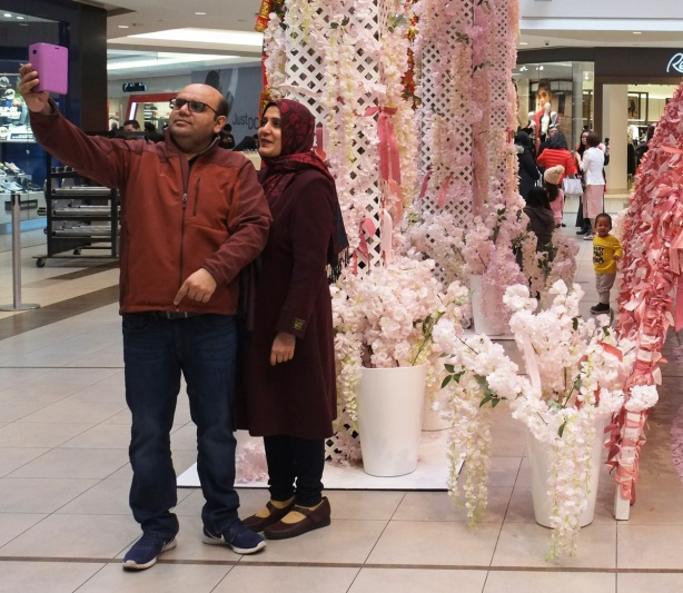 a middle aged muslim couple takes a selfie in front of a lunar new year decoration at Scarborough Town Centre