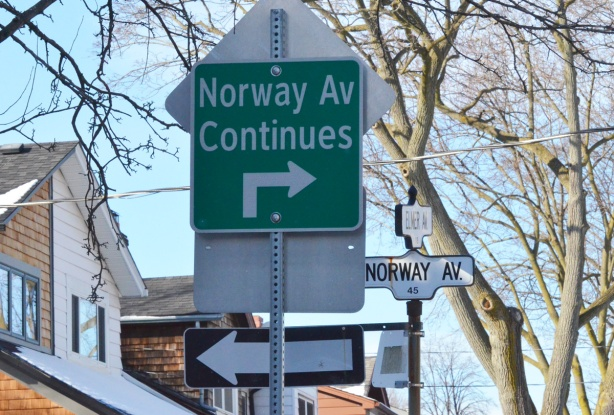 street signs on a post. a one way sign pointing left, a green and white sign that says Norway Ave continues to the right ahead
