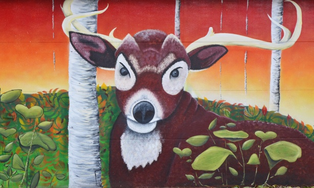 mural of a deer with birch trees painted on a garage