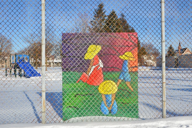 colourful painting behind a chainlink fence in a school yard, winter, snow on the ground around it, picture is of three kids in large yellow hats, playing on green grass
