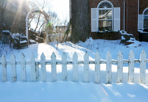 a white picket fence in the snow, wicker chairs in the yard covered with snow