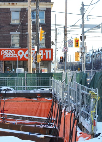 at the intersection of Queen and Woodbine, a hole in the ground on the north east corner and a Pizza Pizza restaurant on the south east corner