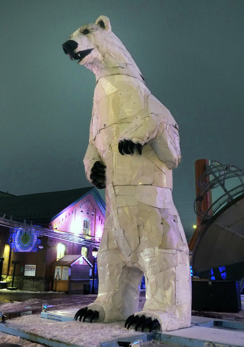 a sculpture of a very large polar bear standing on its hind feet, in white, with black claws and facial features, distillery district, evening