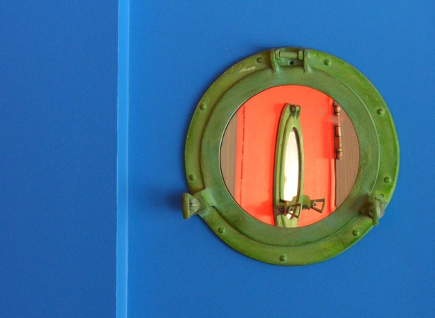 a mirror shaped like a porthole with a green frame, on a bright blue wall, reflection of another porthole but on an orange wall in the mirror