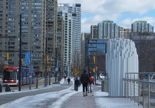 Queens Quay west, street, pedestrians, high rises in the background, a white art installation made of vertical tubes