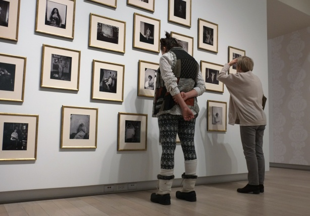 Two women are looking at a wall covered with framed black and white photos at the Ryerson Image Centre
