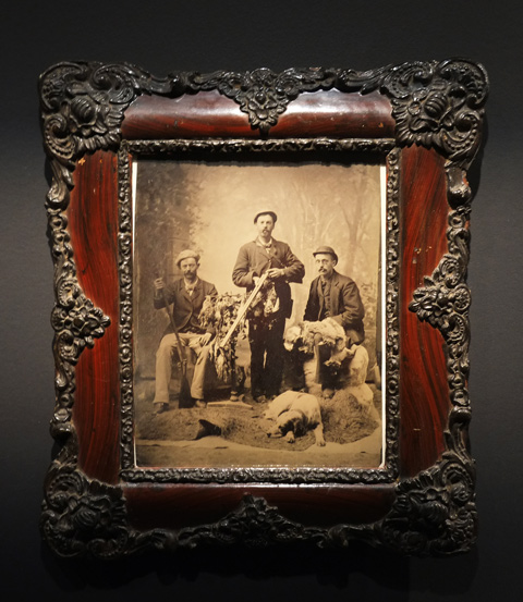 an old tintype photo of three male hunters in sepia tones, framed in an elaborate picture frame and hanging on a dark grey gallery wall