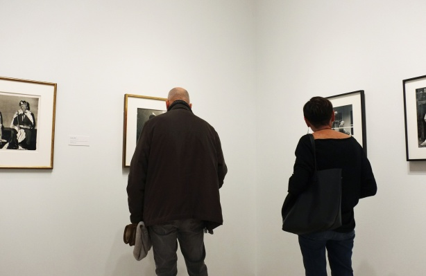 the backs of two people, a man and a woman, as they look at framed photographs hanging on a wall at the Ryerson Image Centre