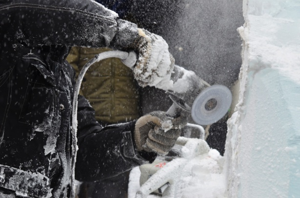 using a power sander, a man is creating a sculpture out of a block of ice