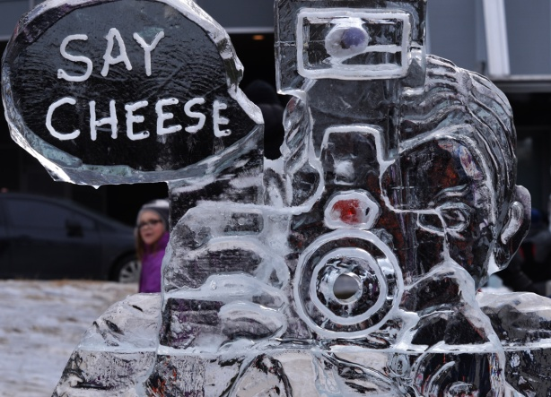 an ice sculpture of a photographer, a person with a camera to his or her eye