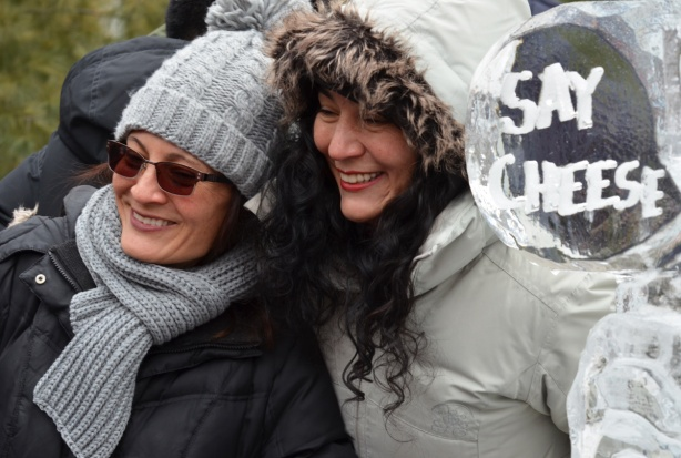 two women pose beside an ice sculpture that says Say Cheese. One woman is wearing a grey toque and scarf and the other woman is wearing a white parka with a fur lined hood