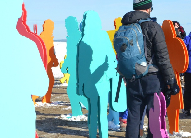 a man and his shadow and many life size cut out figures of people in bright colours