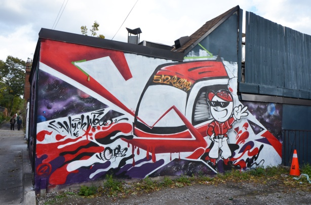 red and white mural of a man (cartoon like) beside a TTC 512 St. Clair street car, in Feel Good Lane
