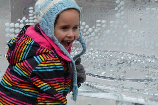 a child ina striped jacket and mouth open wide poses beside an ice sculpture