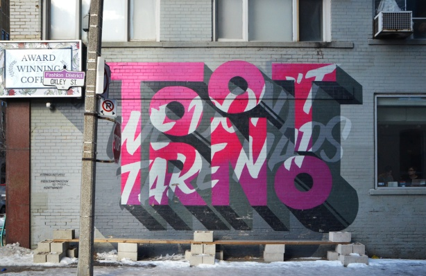 mural in shades of pink and purple that spell the word toronto, superimposed on it are pale grey letters that say we don't take npas, on the side of a grey building,