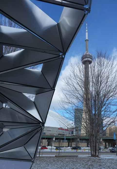 the CN Tower in background, and a leg of art installation in H2O park, Tripix, a three legged arch struture in red and chrome