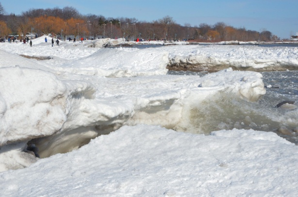 snow and ice accumulations along the shore of Lake Ontario, waves crashing into the shore