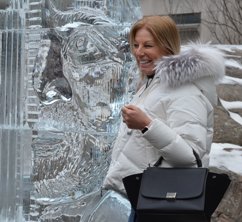 a woman in a white parka with a black handbag poses beside an ice sculpture