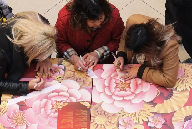 three women writing on pink ribbons