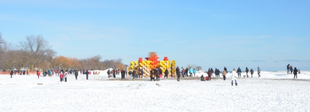 panorama of Woodbine Beach on a February day, art installation in yellows and oranges, lots of people, snow on the ground, winter clothes, Lake Ontario, blue sky with one wispy cloud