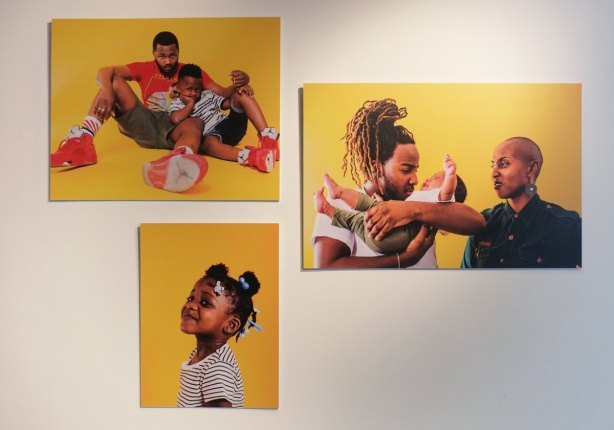 three photos by Yannick Anton hanging on a gallery wall. All three are portraits of black people with bright yellow backgrounds, one is a father and young son, one is a young girls and one is a young child with parents.