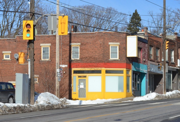 a storefront trimmed in bright yellow and angled at the corner, intersection of Kingston Rd and Brookside