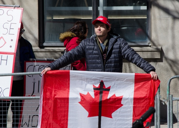 a young man wearing a red MAGA baseball cap holds a Canadian flag on which a black cross has been drawn