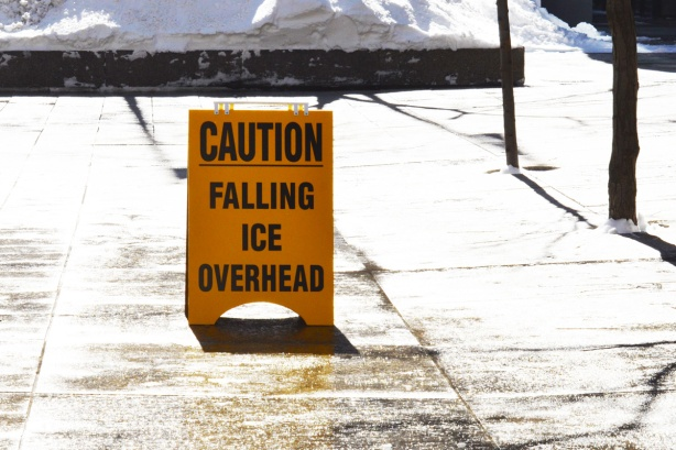 yellow sign on sidewalk that says Caution Falling Ice Overhead