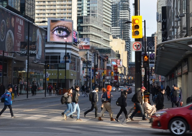 people cross Yonge street on the north side of Dundas, a big picture of an eye is on a billboard looking down over the street