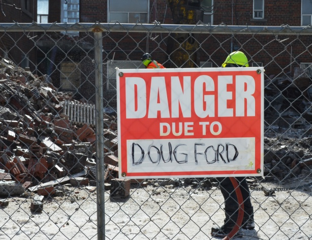 red and white sign, danger due to signs, on a chainlink fence at a construction site in Regent Park, danger due to Doug Ford, premier of Ontario