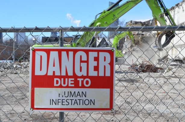 red and white sign, danger due to signs, on a chainlink fence at a construction site in Regent Park, danger due to human infestation