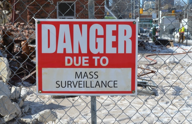 red and white sign, danger due to signs, on a chainlink fence at a construction site in Regent Park, danger due to mass surveillance