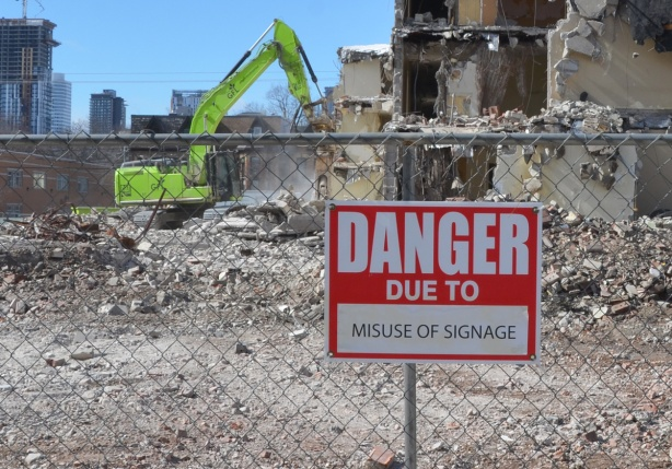 red and white sign, danger due to signs, on a chainlink fence at a construction site in Regent Park, danger due to misuse of signage