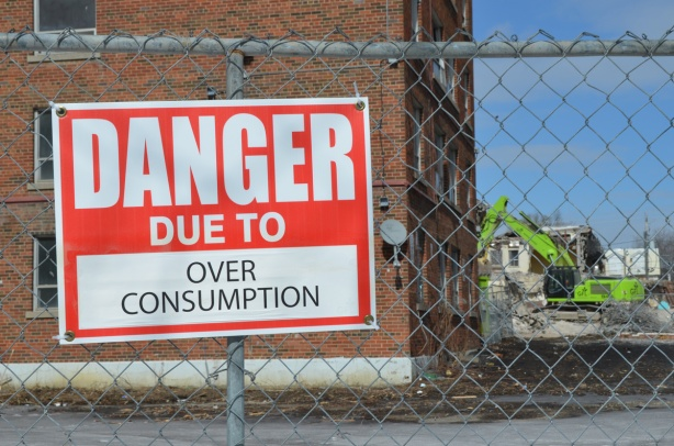 red and white sign, danger due to signs, on a chainlink fence at a construction site in Regent Park, danger due to over consumption