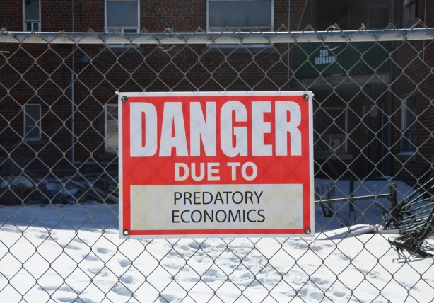 red and white sign, danger due to signs, on a chainlink fence at a construction site in Regent Park, danger due to predatory economics