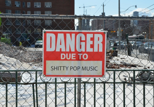 red and white sign, danger due to signs, on a chainlink fence at a construction site in Regent Park, danger due to shitty pop music