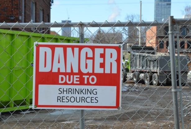 red and white sign, danger due to signs, on a chainlink fence at a construction site in Regent Park, danger due to shrinking resources