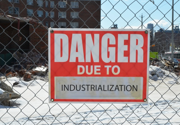 red and white sign, danger due to signs, on a chainlink fence at a construction site in Regent Park, danger due to industrialization