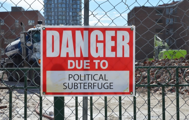 red and white sign, danger due to signs, on a chainlink fence at a construction site in Regent Park, danger due to political subterfuge