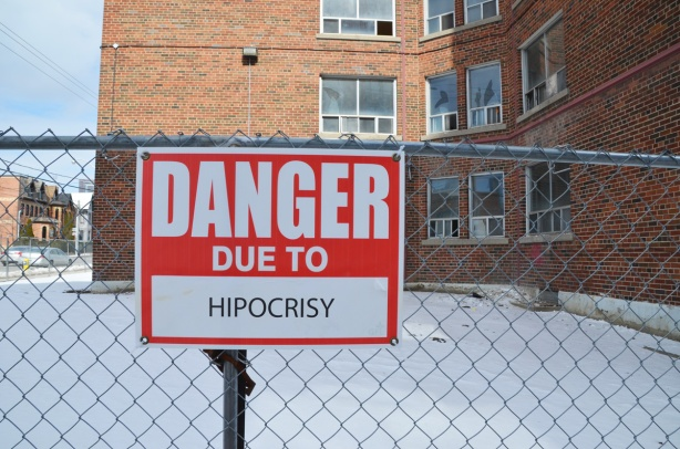 red and white sign, danger due to signs, on a chainlink fence at a construction site in Regent Park, danger due to hypocrisy (but spelled as hipocrisy)