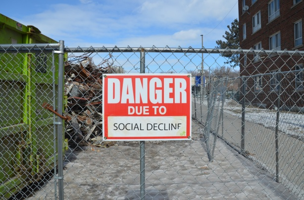 red and white sign, danger due to signs, on a chainlink fence at a construction site in Regent Park, danger due to social decline