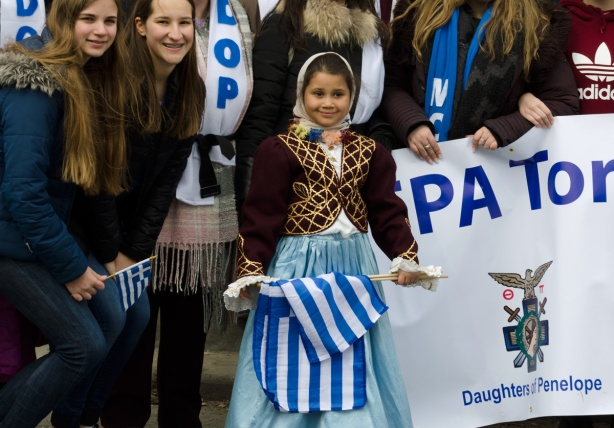 3 girls posing with a banner, the younger girl holds a Greek flag, they are with a banner representing the Daughters of Penelope