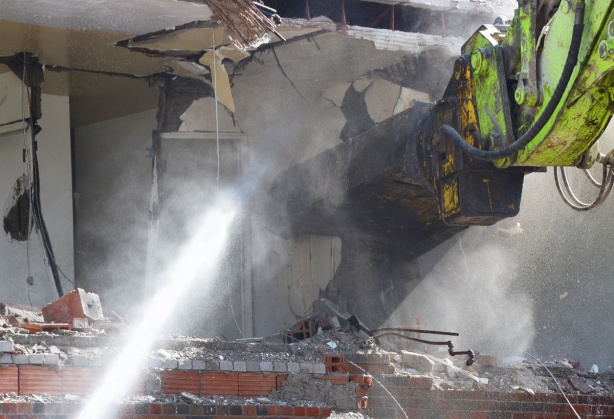 close up of dust and debris as workmen spray water as a machine arm pulls apart a building that is in the process of being demolished