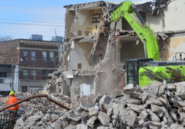 green machinery demolishes a building in Regent Park - one room still has a white fridge in it