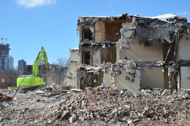 green machinery demolishes a building in Regent Park - 3 storeys remaining