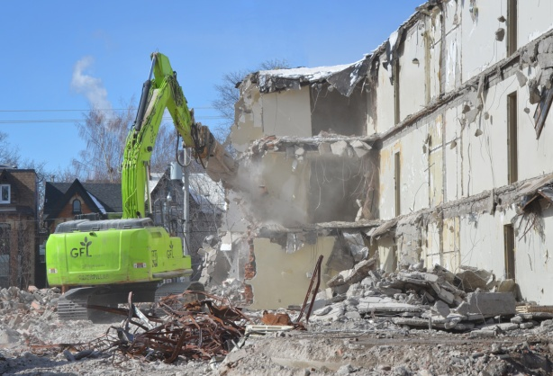green machinery demolishes a building in Regent Park
