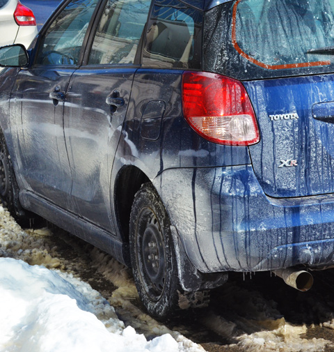 part of a very dirty blue car, parked in the dirty brown slush at the side of a street, snow, winter time,