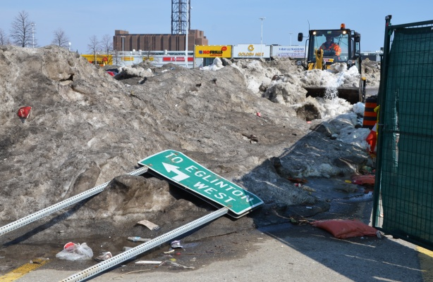 a green street sign for Eglinton Ave lies on the ground, on a pile of dirty snow, a bull dozer is in the background.